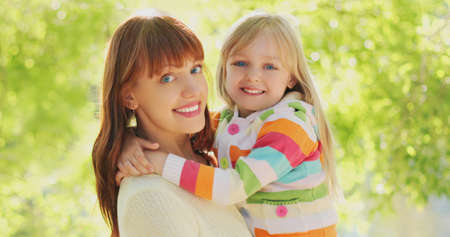 Close up portrait of happy smiling mother and child hugging in summer park
