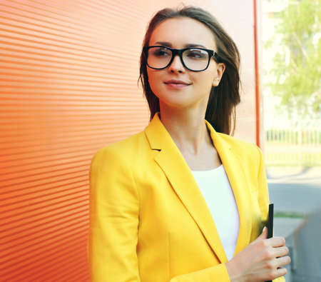 Portrait of young woman wearing a eyeglasses, yellow suit with folder in the city Stok Fotoğraf