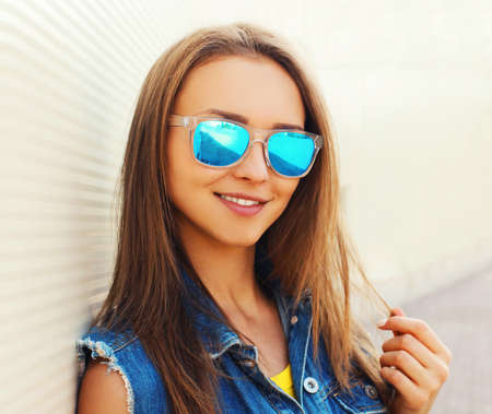 Close up summer portrait of attractive young woman wearing a blue sunglasses in the city Stok Fotoğraf - 155470545