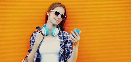 Portrait of young woman with phone in wireless headphones listening to music on orange background Stok Fotoğraf - 155432483