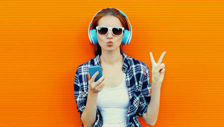 Summer portrait of young woman with phone in a wireless headphones listening to music on an orange wall background