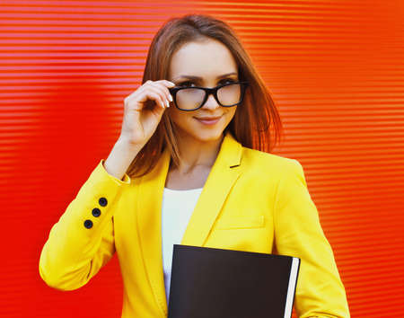 Portrait of young woman wearing a eyeglasses, yellow suit with folder in the city Stok Fotoğraf - 155470554