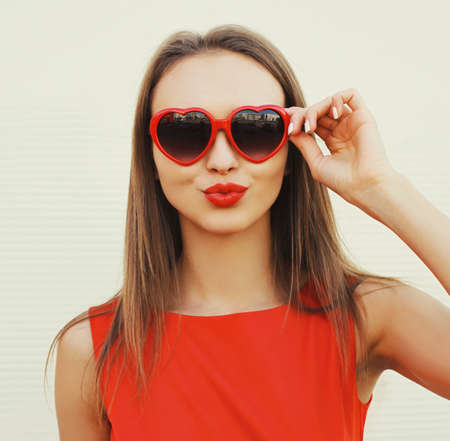 Close up portrait of attractive young woman blowing red lips sending sweet air kiss wearing a heart shaped sunglasses on white background Stok Fotoğraf - 155470556
