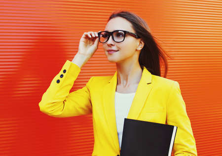 Portrait of young woman wearing a eyeglasses, yellow suit with folder in the city Stok Fotoğraf - 155470558