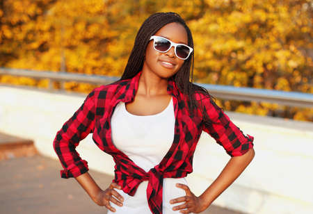 Portrait of young smiling african woman wearing sunglasses in autumn day Stok Fotoğraf