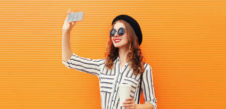 Stylish young smiling woman taking selfie picture by smartphone with coffee cup wearing white striped shirt, black round hat on an orange background Stok Fotoğraf - 156176057