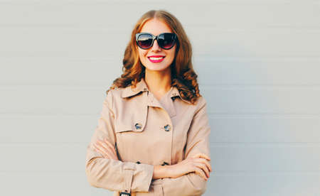 Portrait of beautiful smiling woman wearing a coat, sunglasses in the city over gray background Stok Fotoğraf