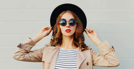 Close up portrait of beautiful woman wearing a coat, sunglasses in the city over gray background