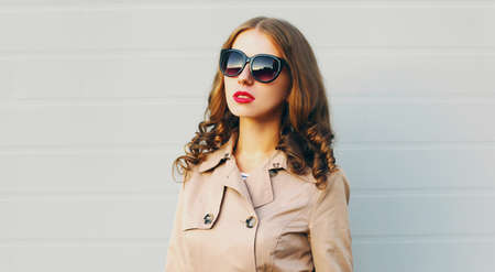 Close up portrait of attractive woman wearing a coat, sunglasses in the city over gray background Stok Fotoğraf - 155759220
