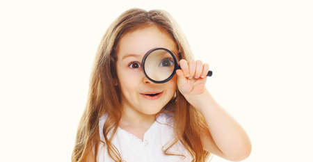 Cute child looking through magnifying glass isolated on a white background