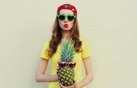 Summer portrait of young woman with pineapple blowing lips wearing a sunglasses over a white background