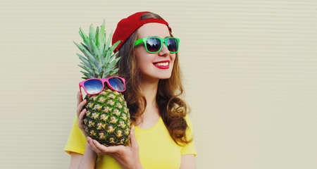 Summer portrait of happy smiling woman with pineapple wearing a sunglasses over a white background