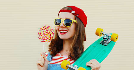Summer portrait of young smiling woman with lollipop and green skateboard wearing a baseball cap on a white background