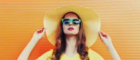 Portrait of attractive woman wearing a summer round hat, sunglasses over an orange background Stok Fotoğraf