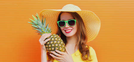 Summer portrait of smiling young woman with pineapple wearing a straw hat, sunglasses over an orange background