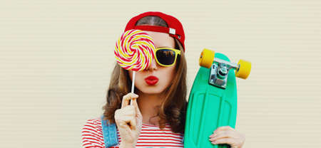 Summer portrait of young woman with lollipop and green skateboard wearing a baseball cap on a white background