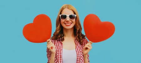 Portrait of happy smiling young woman holding red heart shaped balloon on a blue background