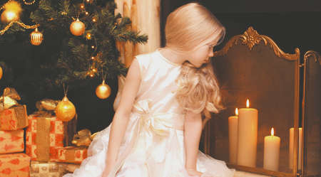 Portrait of little girl child sitting near christmas tree and fireplace at home