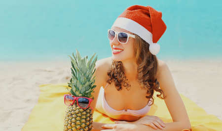 Christmas portrait of happy young smiling woman in red santa hat with funny pineapple lying on a beach together over blue sea background Stok Fotoğraf