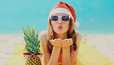 Christmas portrait of young woman blowing lips sending sweet air kiss in red santa hat with pineapple lying on a beach over blue sea background Stok Fotoğraf