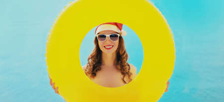 Christmas portrait of happy smiling woman in red santa hat with circle inflatable on a beach over blue sea background