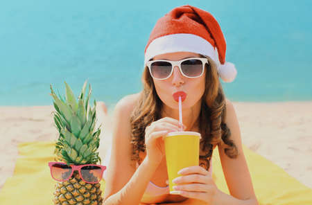 Christmas portrait of happy young woman drinking fresh juice in red santa hat with pineapple lying on a beach over blue sea background Stok Fotoğraf