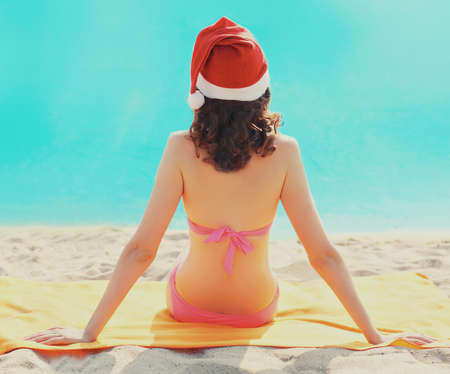 Woman in christmas red santa hat sitting on a sand beach over a blue sea background, rear view