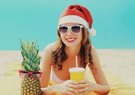 Christmas portrait of happy smiling young woman drinking fresh juice in red santa hat with pineapple lying on a beach over blue sea background Stok Fotoğraf