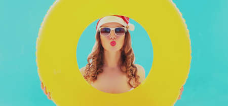 Christmas portrait of young woman in red santa hat blowing lips sending air kiss with circle inflatable on a beach over blue sea background