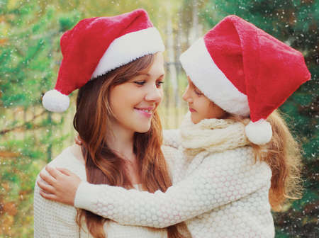 Christmas portrait of happy smiling mother and little girl child in santa red hat outdoors