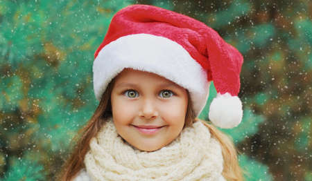Christmas portrait of happy smiling little girl child in santa red hat outdoors Stok Fotoğraf