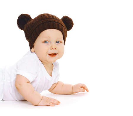 Portrait of happy smiling baby wearing a brown knitted hat with bear ears over a white background