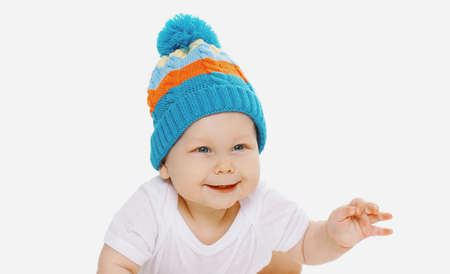 Portrait of happy smiling baby wearing a winter knitted blue hat over a white background Stok Fotoğraf