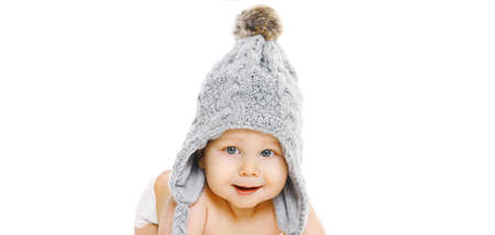 Portrait of happy smiling baby wearing a winter knitted gray hat over a white background Stok Fotoğraf