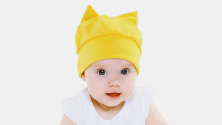 Portrait close up of cute baby wearing a yellow hat over a white background