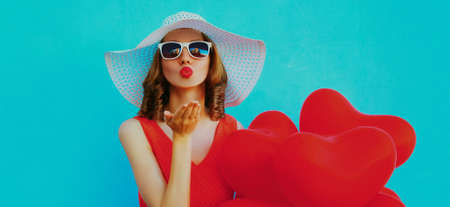 Portrait of beautiful woman with bunch of red heart shaped balloons blowing lips sending sweet air kiss wearing a summer straw hat, sunglasses on a blue background