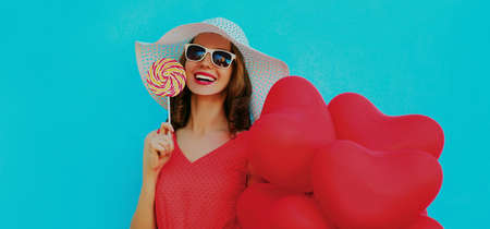 Portrait of happy smiling woman holding lollipop and bunch of red heart shaped balloons wearing a summer straw hat, sunglasses on a blue background