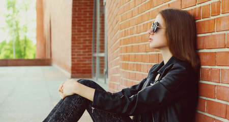 Young woman in casual sitting in the city wearing a black rock style over a brick wall background Stok Fotoğraf