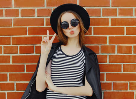Portrait of stylish young woman model wearing a black rock style over a brick wall background