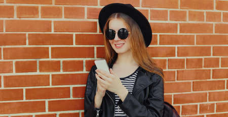 Portrait of stylish young woman with phone over a brick wall background