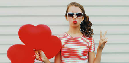 Portrait of young woman with red heart shaped balloon blowing lips sending sweet air kiss wearing a sunglasses on a white background