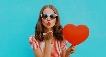 Portrait of beautiful woman with red heart shaped balloon blowing lips sending sweet air kiss wearing a sunglasses on a blue background