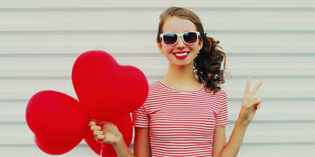 Portrait of happy smiling young woman with bunch of red heart shaped balloons on a white background Stok Fotoğraf