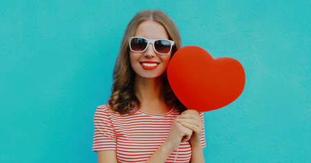 Portrait of happy young woman holding red heart shaped balloon wearing a sunglasses on a blue background