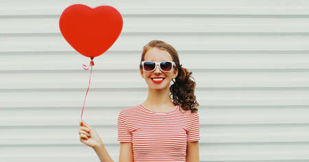 Portrait of happy smiling young woman with red heart shaped balloon on a white background