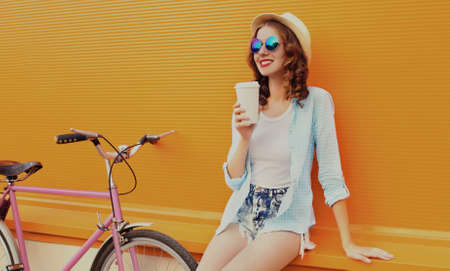 Portrait of happy young smiling woman with bicycle and cup of juice or coffee on an orange background