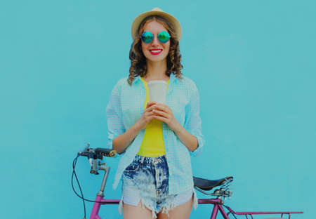 Portrait of happy young smiling woman with bicycle and cup of juice or coffee on a blue background