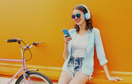 Portrait of happy young smiling woman with phone listening to music in headphones with bicycle on an orange background