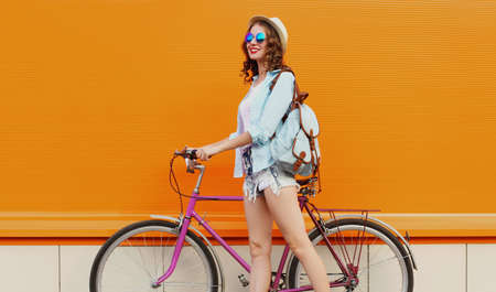 Happy young smiling woman with bicycle on an orange background
