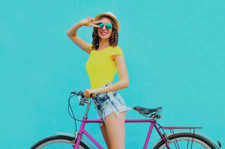 Happy young smiling woman with bicycle on a blue background